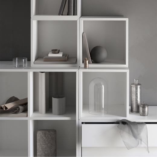 Close-up of a white storage combination that consists of open cubes in two different depths, cabinet with drawers and cabinet with doors.