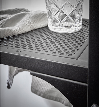 Close-up of a black mesh shelf with a glass and a light grey table napkin.