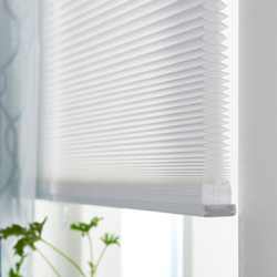 Close-up of a white cellular blind with honeycomb structure that creates a layer of insulation.
