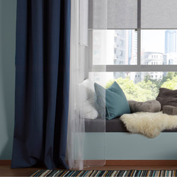 A living room featuring large windows with a cosy seating area decorated with three layers of curtains. One layer of grey roller blinds that stops reflections on screens, one layer of white sheer curtains that filters the daylight and one layer of blue curtains for privacy.