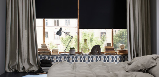 A bedroom featuring large windows with black block-out roller blinds and one layer of thick grey curtains for cosiness and silence.