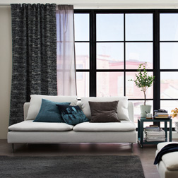 A living room featuring large mullion windows with one layer of white and gray sheer curtains that filters the daylight and one layer of black block-out curtains for privacy.