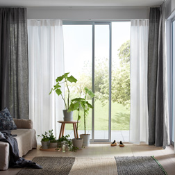 A bright living room featuring large sliding windows with two layers of white and beige sheer panel curtains that filters the daylight and one layer of dark grey thick curtains for privacy.