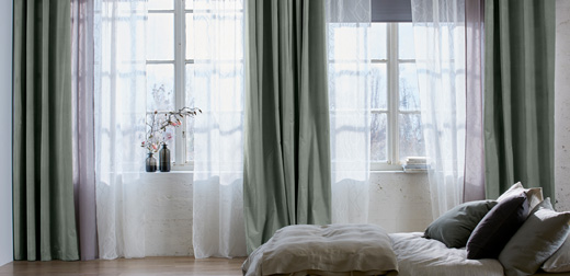 A bright bedroom featuring mullion windows with black block-out roller blinds, one layer of sheer white curtains that filters the daylight and one layer of grey-green thick curtains for privacy.