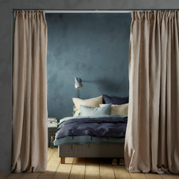 A doorway with beige linen curtains, used as room divider to separate the small bedroom from the living room.