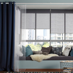 A living room featuring large windows with a cozy seating area decorated with three layers of curtains. One layer of gray roller blinds that stops reflections on screens, one layer of white sheer curtains that filters the daylight and one layer of blue curtains for privacy.