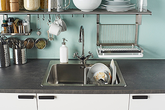 A stainless steel wall shelf, above a kitchen sink, with hooks for cups and kitchen utensils close at hand, a shelf for spices and a dish drainer.