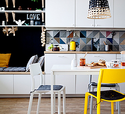 A white kitchen with beech worktops, shown together with a white dining table and chairs in white and yellow.