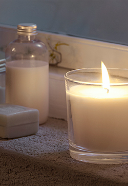 Scented candle light on the windowsill for relaxation.