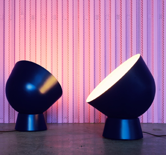 Two dark blue floor lamps, inspired by old military searchlights.