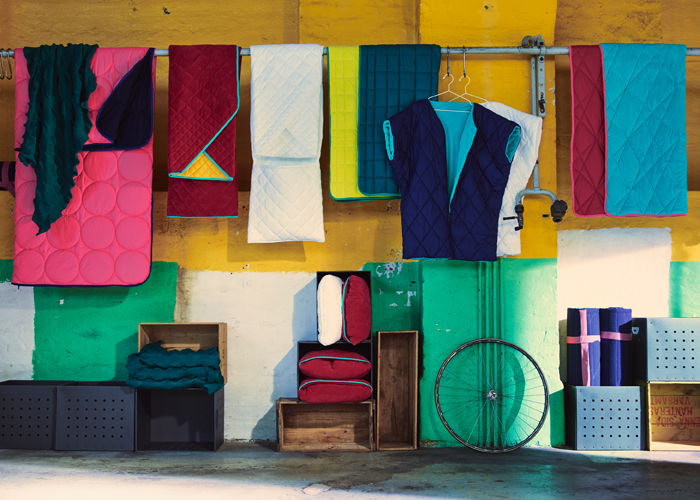 A display of quilted throws in pink, red, white, yellow, green and turquoise, shown together with a quilted jacket without arms in dark blue and white.