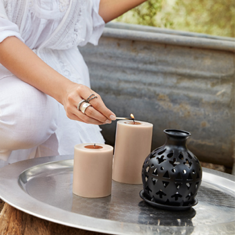 A woman lighting two block candles on a steel tray, shown outdoors together with a black lantern with punch pattern.