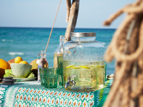 A large glass jar with tap filled with water and fresh lemons. Shown outdoors together with green glasses, glass bottles and green stoneware bowls.