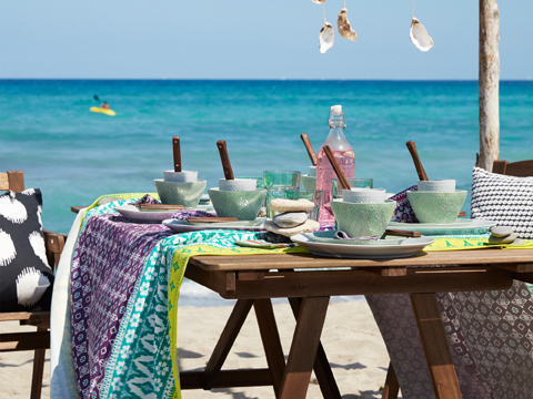 An outdoor table on the beach, with stoneware bowls and plates in light grey and green shown together with a colourful tablecloth with batik pattern.