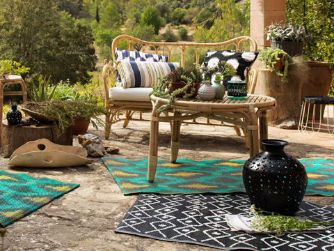 A patio with sofa and table made of rattan and colourful rugs with batik patterns.