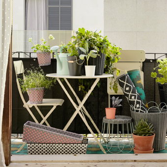 A small balcony furnished with a beige round table and a chair, both are foldable. Shown together with plant pots in different sizes and colours and lots of green plants.