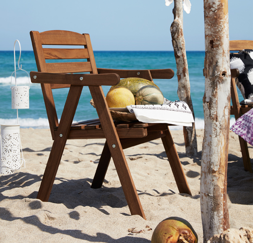 An outdoor chair with armrests, on the beach, shown together with different sorts of melons in a bowl.