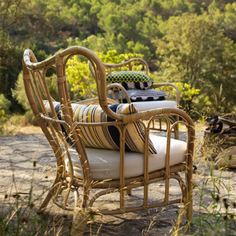 A patio with a rattan armchair with a white seat cushion and an extra striped cushion for lumbar support.