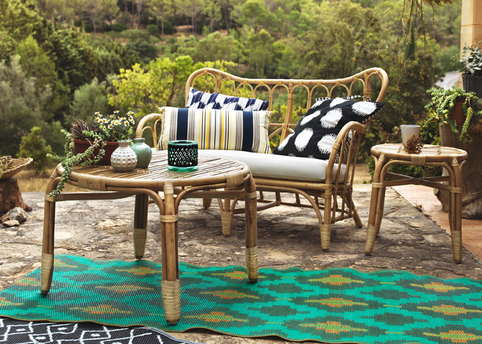 A patio with sofa and table made of rattan and a colourful rug with batik pattern.