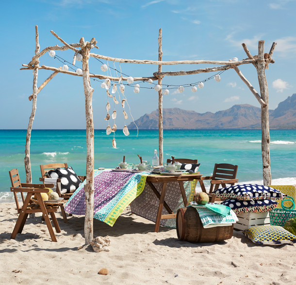 Outdoor chairs and a table on the beach, with a colourful tablecloth with batik pattern and colourful cushions.