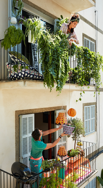 A woman on a balcony hauling down a picnic hamper on a rope to a man on the balcony below. The women's balcony is decorated with colourful cushions and lots of green plants and the man's balcony is furnished with solar-powered lamps, a bench, a table, a grill and green plants.