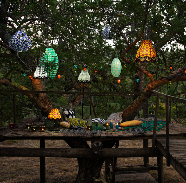 Solar-powered pendant lamps in different shapes and colours, hanging outdoors in a tree.
