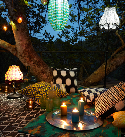 A round stainless steel tray with lit candles in different sizes. Shown outdoors together with solar-powered lamps, rugs and cushions in colourful patterns.