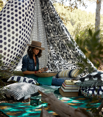 A woman sitting outside, under an improvised tent, made of curtains with different black and white patterns. And she is surrounded with lots of cushions in colourful patterns.
