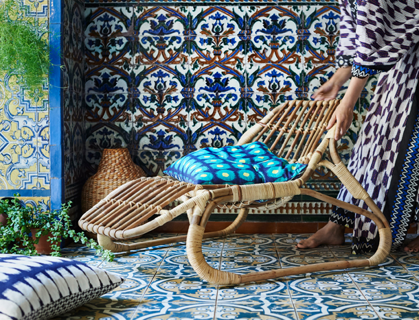 A small curvy lounger made of rattan. Shown with a colourful cushion with batik inspired pattern.