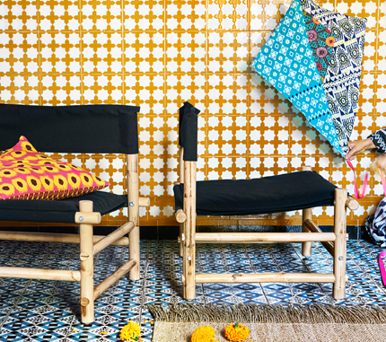 Two low handmade easy chairs made of rattan with black cotton seat and back.