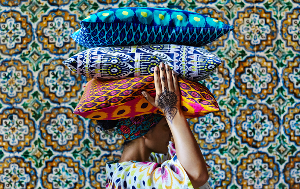 A woman with henna tattoos on her hands, carrying colorful cushions with batik inspired patterns, on her head.