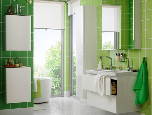 Green and white bathroom with double bowl sink with two drawers.