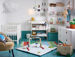 Blue and white nursery with white crib, changing table and chest-of-drawers.