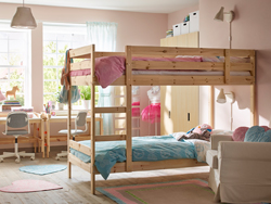 Pine bunk bed in shared children's bedroom with pink walls.