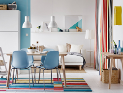 Colourful open plan dining and sitting room with light wood table and blue chairs.