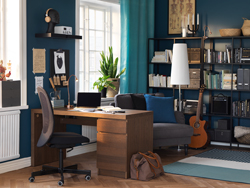 A wooden desk with drawers in an office / study with blue walls.