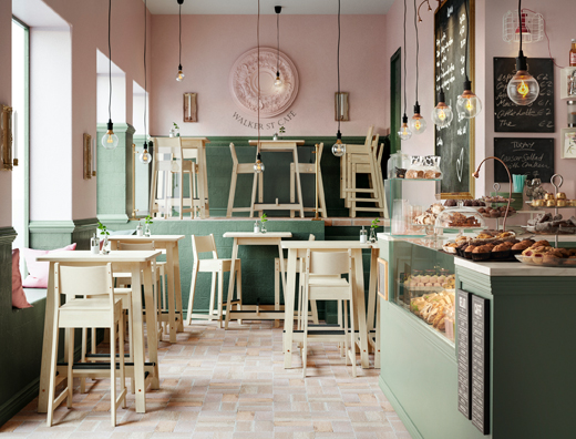 A pink and green cafe with wooden bar tables and stools.