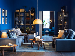 Blue living room with glass-fronted cabinets and two blue sofas, one with chaise-longues.