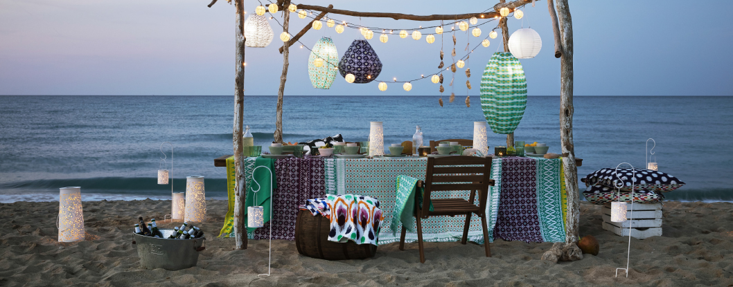Outdoor chairs and table on the beach, with solar-powered lamps, textiles and tableware from the SOMMAR 2017 summer collection.