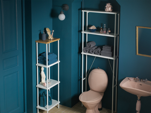 A blue bathroom with a free-standing shelf unit in white with a top shelf in bamboo. And a wall-mounted open storage above the toilet with toilet articles and extra towels.