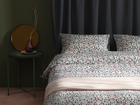 A bed with quilt cover and two pillowcases made of 100% cotton, with a dotted pattern in blue, grey, beige and apricot, that looks like strokes of watercolours.