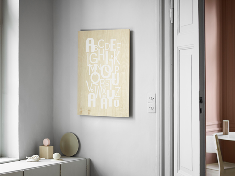 A white wall with a wooden picture with the Swedish alphabet printed in white block letters in a playful way.