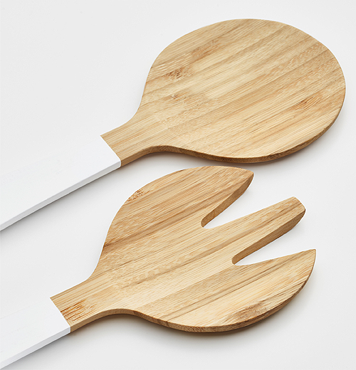 Close-up of bamboo salad servers with white handles.