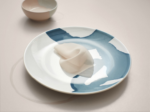 A plate in earthenware featuring a pattern of flowing watercolours in turquoise tones.
