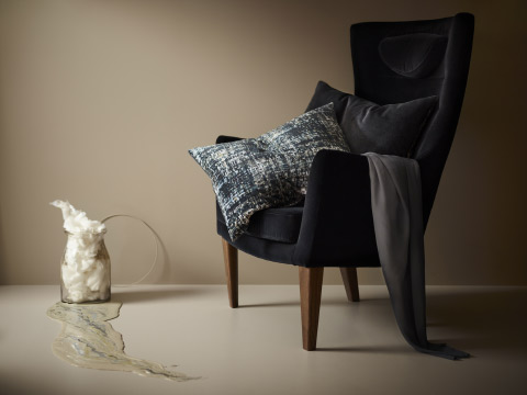 Two cushions shown in an armchair, made in cotton velvet with dark colours blended together like an oil painting and with a backside in solid grey.