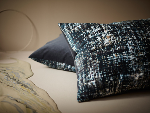 Two cushions shown on the floor, made in cotton velvet with dark colors blended together like an oil painting and with a backside in solid grey.