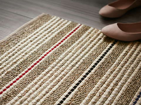 Close-up of a flatwoven rug with stripes in natural, beige, black and red. The rug is made of seagrass, palm leaf and jute that makes it hard-wearing and recyclable.