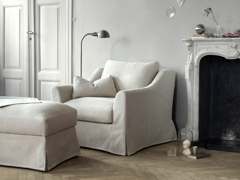 A light living room with a generous sized armchair that has an additional loose cushion, shown together with a footstool that features hidden storage, both have a beige cover in a cotton/linen blend.