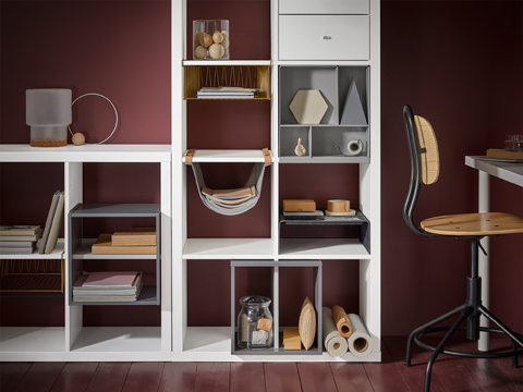 A white shelving unit filled with different inserts, such as brass-colored wire baskets, hanging organiser with leather straps, light grey shelf dividers and storage with compartments.
