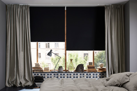 A living room featuring large windows with black black-out roller blinds and one layer of thick grey curtains for cozyness and silence.